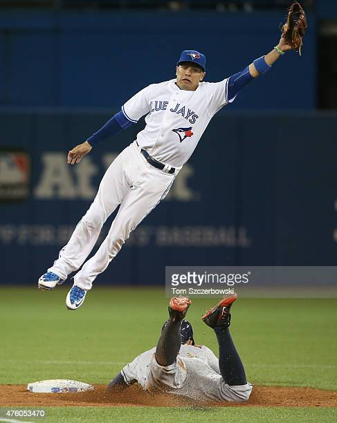 George Springer of the Houston Astros steals second base in the ninth inning during MLB game action as Ryan Goins of the Toronto Blue Jays jumps for...