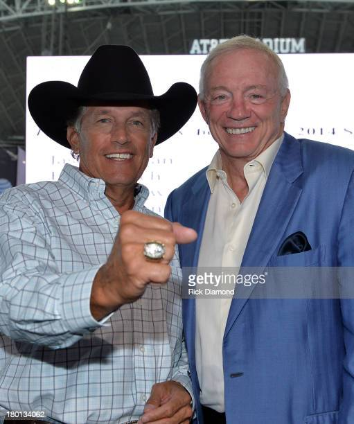 George Strait tries on Jerry Jones Dallas Cowboys Super Bowl ring during the press conference for the 2014 The Cowboy Rides Away tour at Dallas...