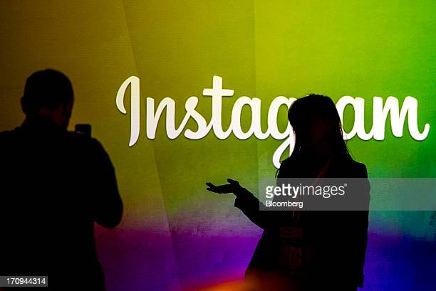 George Sylvain left takes a photograph of Tara Shi while standing in front of the Instagram Inc logo during an event at Facebook Inc headquarters in...