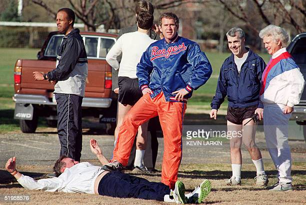 George W Bush son of the US President George Bush playfully steps upon his father 27 January 1990 while he warms up for a run at Fort McNaire Army...
