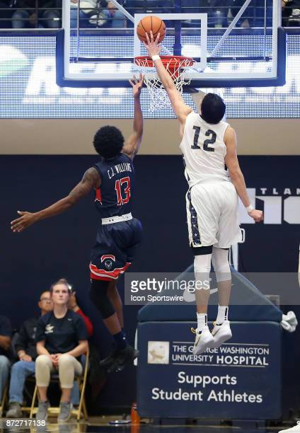 George Washington Colonials guard Yuta Watanabe shoots over Howard Bison forward Charles Williams during a men's college basketball game between the...