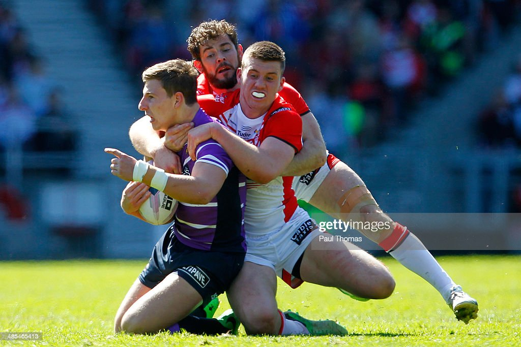 George Williams (L) of Wigan is tackled by Paul Wellens and Joe Greenwood (R) of St Helens during the Super League match between St Helens and Wigan Warriors at Langtree Park on April 18, 2014 in St Helens, England.
