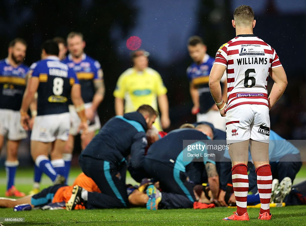 George Williams of Wigan Warriors looks on as medics attend Mitchell Achurch of Leeds Rhinos during the Round 2 match of the First Utility Super League Super 8s between Leeds Rhinos and Wigan Warriors at Headingley Carnegie Stadium on August 14, 2015 in Leeds, England.