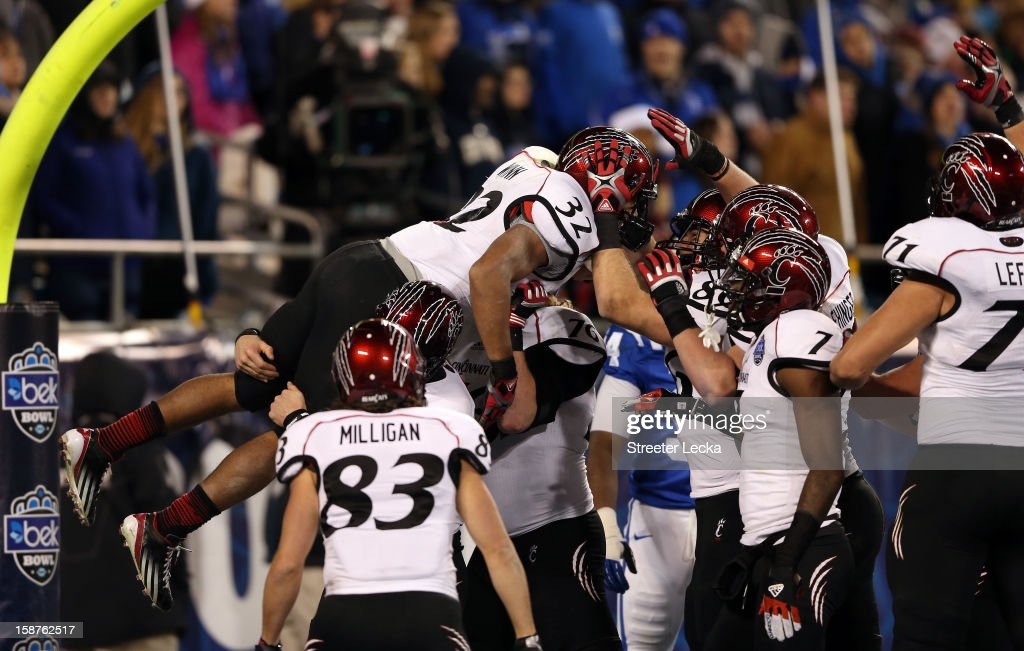 George Winn #32 of the Cincinnati Bearcats celebrates with teammates after running for a touchdown against the Duke Blue Devils during their game at Bank of America Stadium on December 27, 2012 in Charlotte, North Carolina.