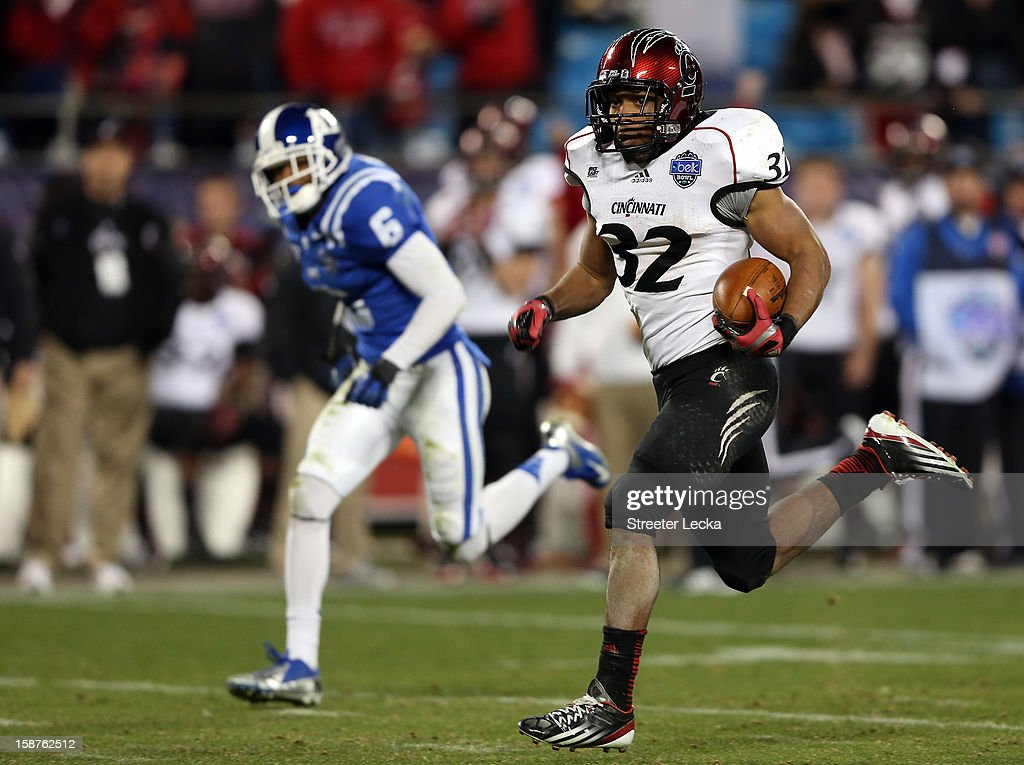 George Winn #32 of the Cincinnati Bearcats runs for a touchdown as Ross Cockrell #6 of the Duke Blue Devils tries to catch him during their game at Bank of America Stadium on December 27, 2012 in Charlotte, North Carolina.