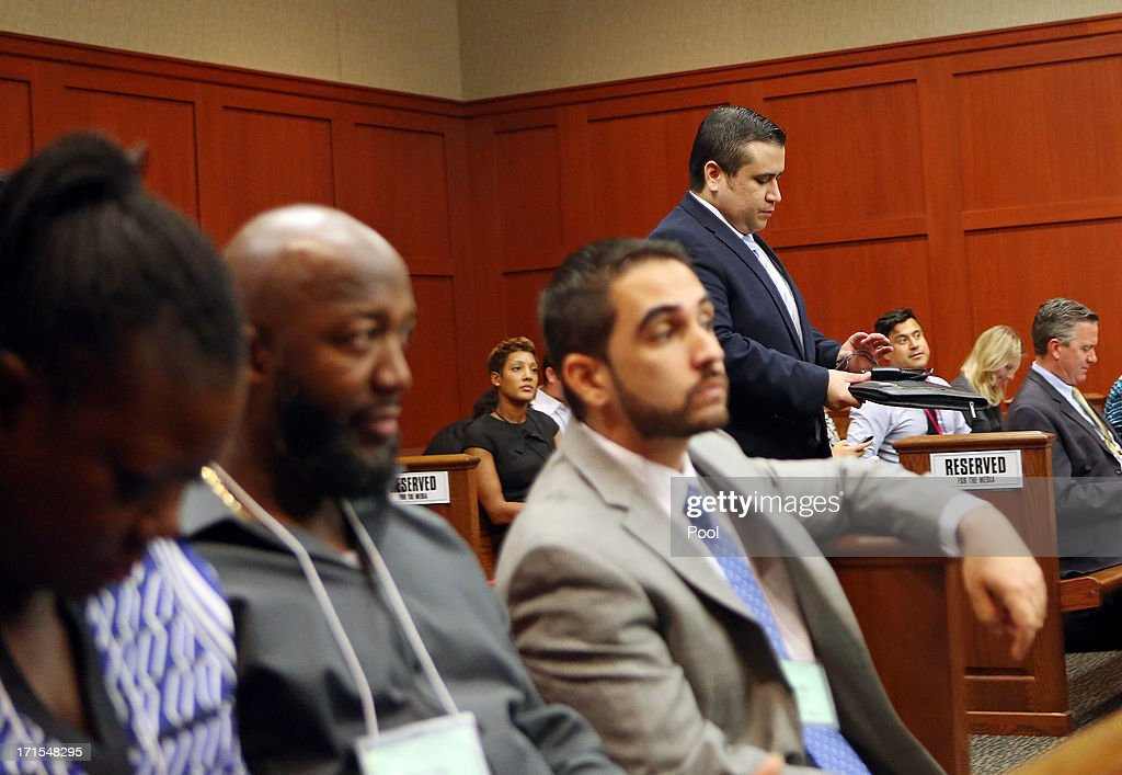 George Zimmerman walks past Trayvon Martin's parents Sybrina Fulton, left and Tracy Martin, second from left, as he reenters the courtroom after lunch recess during Zimmerman's trial in Seminole circuit court June 26, 2013 in Sanford, Florida. Zimmerman is charged with second-degree murder for the February 2012 shooting death of 17-year-old Trayvon Martin.