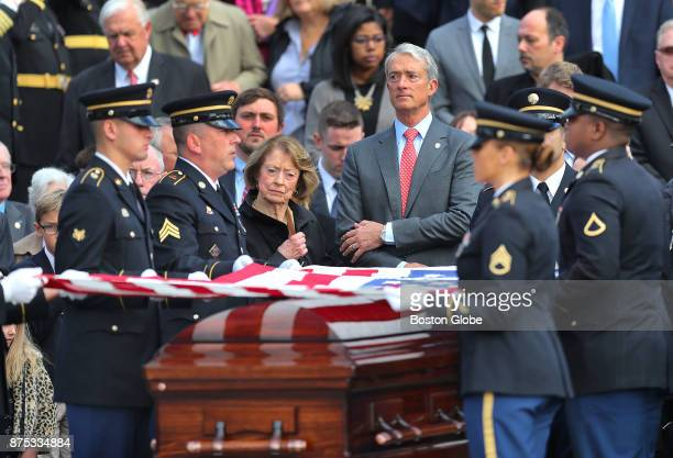 Georgea Hudner center left the widow of Medal of Honor recipient Thomas Hudner looks on as the Army National Guard pallbearers fold an American flag...