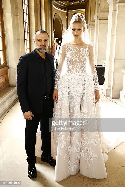Georges Hobeika poses with a model backstage during the Georges Hobeika Haute Couture Fall/Winter 20162017 show as part of Paris Fashion Week on at...