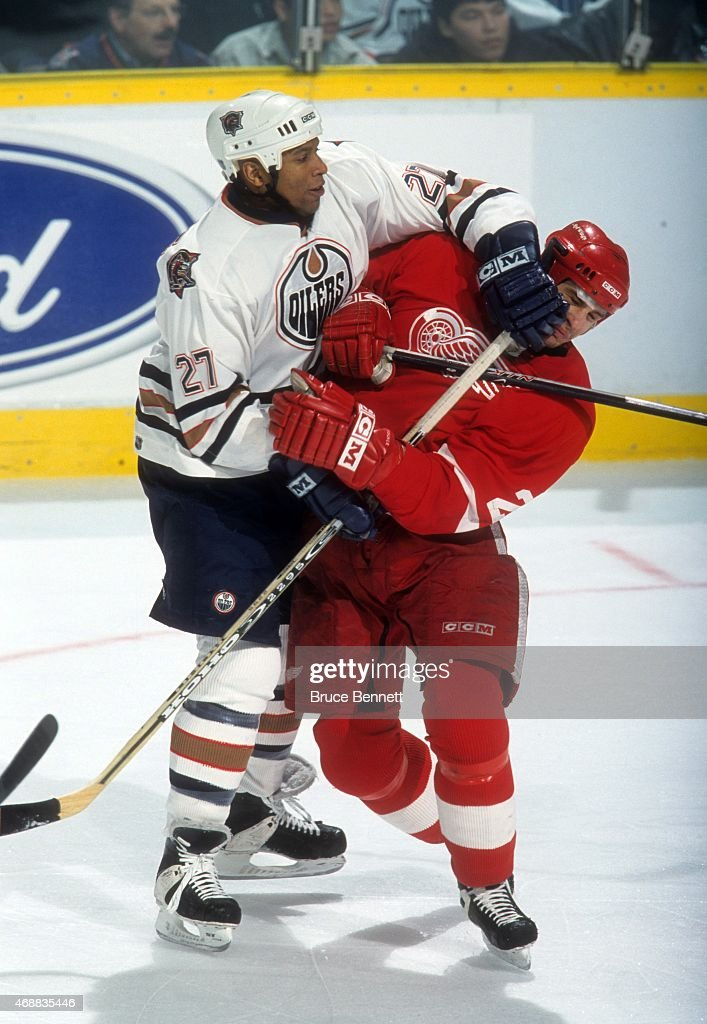 Georges Laraque of the Edmonton Oilers checks Jiri Fischer of the Detroit Red Wings on January 20 2001 at Rexall Place in Edmonton Alberta Canada