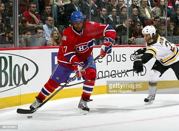 Georges Laraque of the Montreal Canadiens skates against Steve Montador of the Boston Bruins during Game Four of the Eastern Conference Quarterfinal...