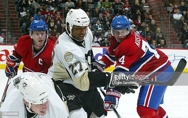 Georges Laraque of the Pittsburgh Penguins battles with both Saku Koivu and Sergei Kostitsyn of the Montreal Canadiens during their NHL game at the...