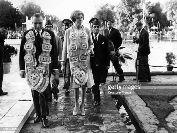 Georges Pompidou et sa femme Claude Pompidou le cou charge de guirlandes se promenent dans les allees des Jardins de Shalimar le 9 fevrier 1965 a...