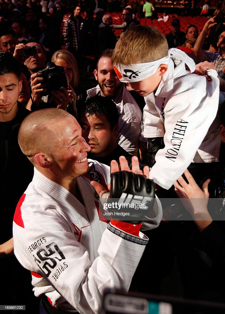 Georges St-Pierre greets a young fan on his way out of the arena after his victory over Nick Diaz in their welterweight championship bout during the UFC 158 event at Bell Centre on March 16, 2013 in Montreal, Quebec, Canada.
