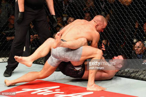 Georges StPierre of Canada takes down Michael Bisping of England in their UFC middleweight championship bout during the UFC 217 event at Madison...