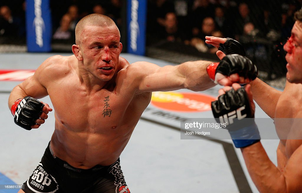 Georges St-Pierre punches Nick Diaz in their welterweight championship bout during the UFC 158 event at Bell Centre on March 16, 2013 in Montreal, Quebec, Canada.