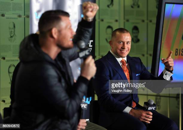 Georges StPierre reacts as Michael Bisping speaks to the media during the UFC 217 press conference at the Hockey Hall of Fame on October 13 2017 in...
