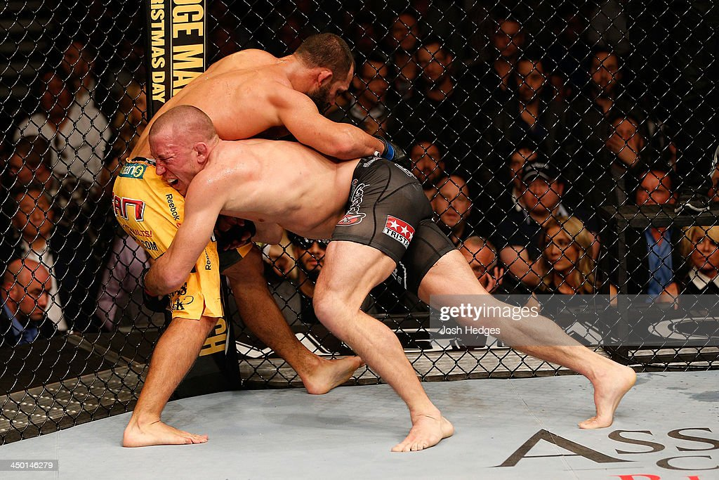 <a gi-track='captionPersonalityLinkClicked' href=/galleries/search?phrase=Georges+St-Pierre&family=editorial&specificpeople=4864241 ng-click='$event.stopPropagation()'>Georges St-Pierre</a> (black shorts) takes down Johny Hendricks in their UFC welterweight championship bout during the UFC 167 event inside the MGM Grand Garden Arena on November 16, 2013 in Las Vegas, Nevada.