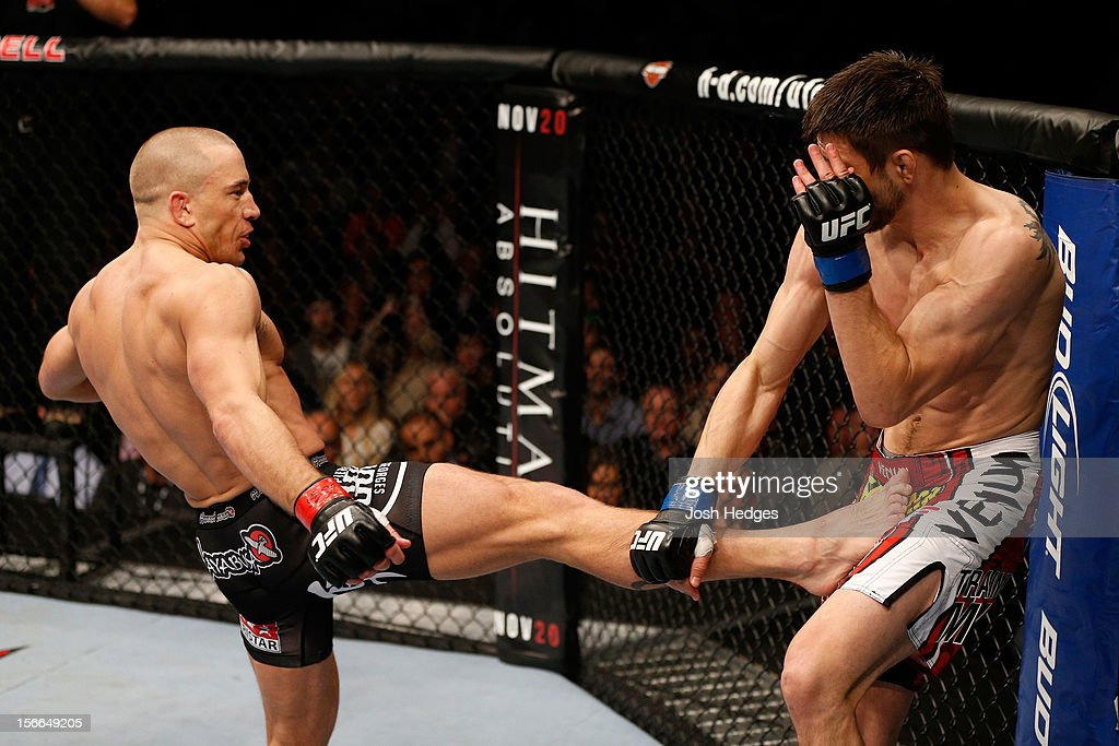 Georges St-Pierre (L) throws a kick against Carlos Condit in their welterweight title bout during UFC 154 on November 17, 2012 at the Bell Centre in Montreal, Canada.