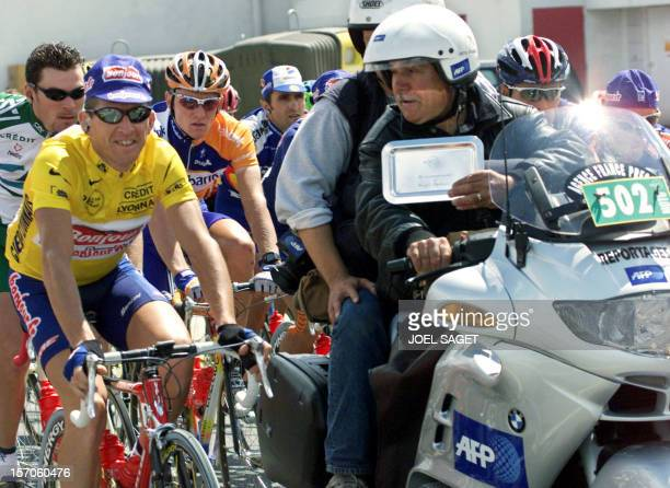 Georges Stylianos poses with the yellow jersey French François Simon of the Bonjour team as the Agence France Presse' s motorcyclist received the...