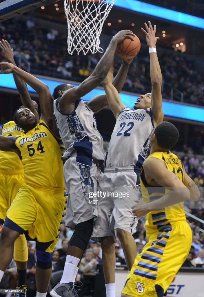 Georgetown center Moses Ayegba (32) pulls down a rebound over teammate Otto Porter (22) and Marquette forward Davante Gardner (54) in the first half at the Verizon Center in Washington, D.C., Monday, February 11, 2013.