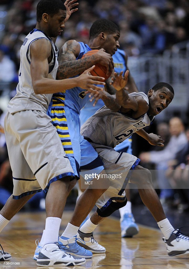 Georgetown forward Hollis Thompson (1), left, and Georgetown guard Jason Clark (21) tie up Marquette guard Vander Blue (2) during second-half action at the Verizon Center in Washington, D.C., Wednesday, January 4, 2012. Georgetown beat Marquette, 73-70.
