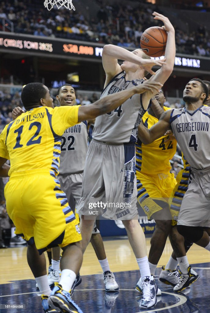 Georgetown forward Nate Lubick (34) gets fouled by Marquette guard Derrick Wilson (12) during a battle for a rebound in the second half at the Verizon Center in Washington, D.C., Monday, February 11, 2013. Georgetown defeated Marquette, 63-55.