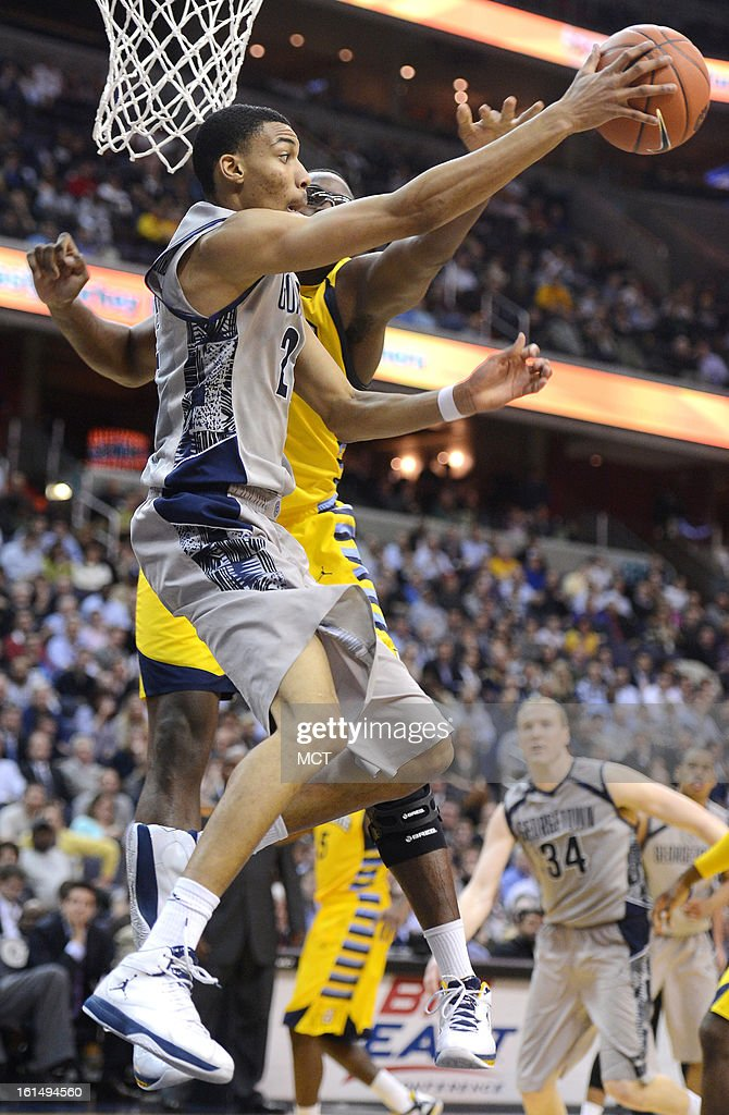 Georgetown forward Otto Porter Jr. (22) dishes the ball off while under defensive pressure from Marquette center Chris Otule (42), back, in the second half at the Verizon Center in Washington, D.C., Monday, February 11, 2013. Georgetown defeated Marquette, 63-55.