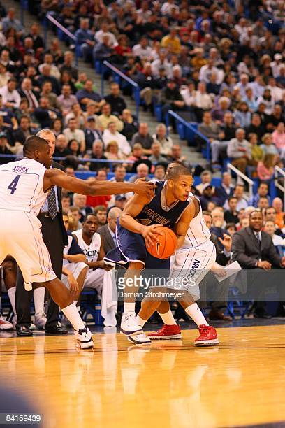Georgetown guard Chris Wright breaks the defense of Connecticut forward Jeff Adrien and Kemba Walker NCAA Basketball Georgetown at UConn Monday game...