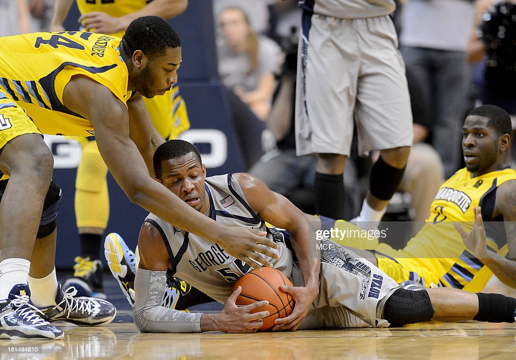 Georgetown guard Jabril Trawick (55) covers up a loose ball, as Marquette forward Davante Gardner (54) reaches for the ball, in the second half at the Verizon Center in Washington, D.C., Monday, February 11, 2013. Georgetown defeated Marquette, 63-55.