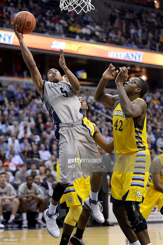 Georgetown guard Markel Starks (5) splits between Marquette forward Marquette forward Steve Taylor, Jr. (25), back, Marquette center Chris Otule (42) in the second half at the Verizon Center in Washington, D.C., Monday, February 11, 2013. Georgetown defeated Marquette, 63-55.