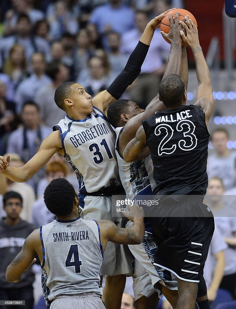 Georgetown guard Stephen Domingo (31) and Georgetown center Moses Ayegba (32), center, and High Point guard Devante Wallace (23) reach for a rebound in the second half at the Verizon Center in Washington, Thursday, Dec. 5, 2013. Georgetown beat High Point, 80-45.