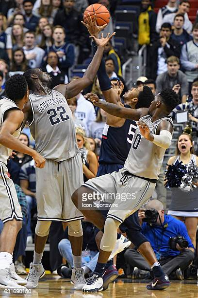 Georgetown Hoyas guard LJ Peak and forward Akoy Agau fight for rebound against Connecticut Huskies forward Vance Jackson late in the second half on...