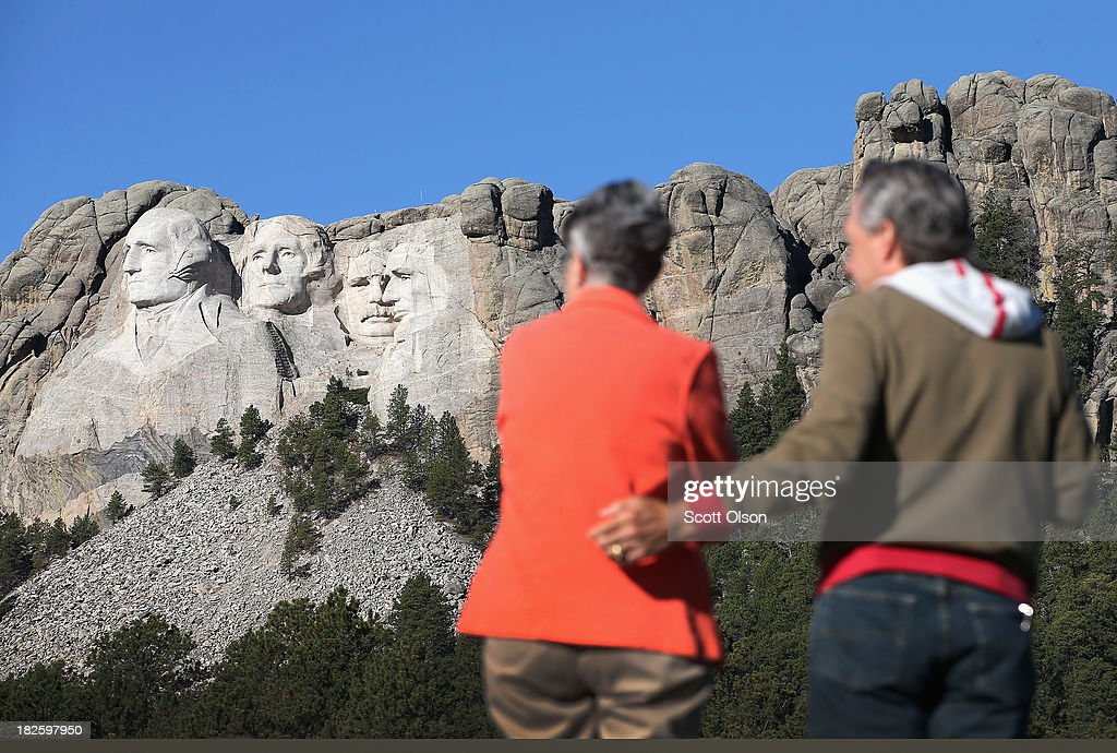 Georgia (L) and Keith Ormand stop to take a picture near the entrance to Mount Rushmore National Memorial on October 1, 2013 in Keystone, South Dakota. The couple had travelled from Gowensville, South Carolina to visit the memorial but, Mount Rushmore and all other national parks were closed today after congress failed to pass a temporary funding bill, forcing about 800,000 federal workers off the job. A bulletin issued by the Department of Interior states, 'Effective immediately upon a lapse in appropriations, the National Park Service will take all necessary steps to close and secure national park facilities and grounds in order to suspend all activities ...Day use visitors will be instructed to leave the park immediately...'