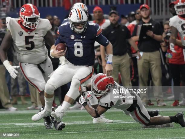 Georgia Bulldogs defensive back Dominick Sanders tackles Auburn Tigers quarterback Jarrett Stidham during the SEC Championship game between the...
