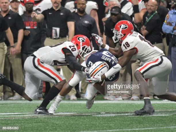 Georgia Bulldogs defensive back JR Reed and Georgia Bulldogs defensive back Deandre Baker tackle Auburn Tigers wide receiver Ryan Davis during the...