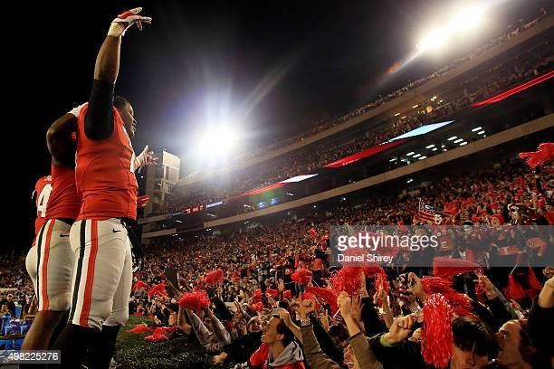 Georgia Bulldogs players celebrate with fans after beating the Georgia Southern Eagles in overtime at Sanford Stadium on November 21 2015 in Athens...
