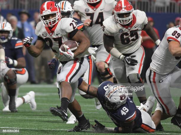 Georgia Bulldogs running back Nick Chubb escapes the reach of Auburn Tigers linebacker Darrell Williams during the SEC Championship game between the...