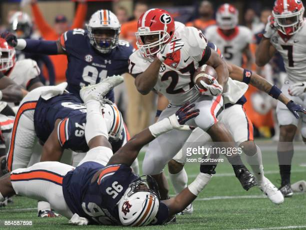 Georgia Bulldogs running back Nick Chubb looks for running room as Auburn Tigers defensive linemen Dontavius Russell reaches to tackle him during the...