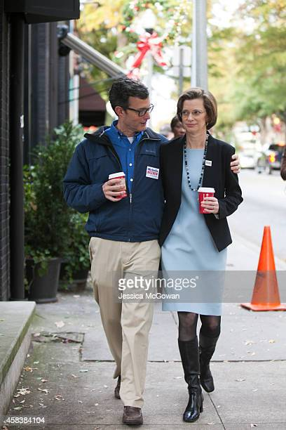 Georgia Democratic US Senate candidate Michelle Nunn and husband Ron Martin walk down the street on Election Day on November 4 2014 in Decatur...