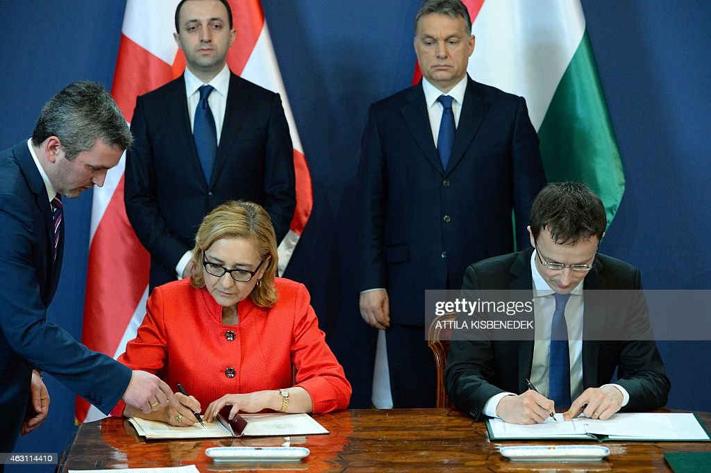 Georgia Foreign Minister Tamar Beruchashvili (L down) and her Hungarian counterpart Peter Szijjarto (R down) sign a cooperation agreement between their countries in front of their Prime Ministers, <a gi-track='captionPersonalityLinkClicked' href=/galleries/search?phrase=Viktor+Orban&family=editorial&specificpeople=4685765 ng-click='$event.stopPropagation()'>Viktor Orban</a> (R) of Hungary and <a gi-track='captionPersonalityLinkClicked' href=/galleries/search?phrase=Irakli+Garibashvili&family=editorial&specificpeople=11579652 ng-click='$event.stopPropagation()'>Irakli Garibashvili</a> (L) of Georgia in Delegation Hall of the parliament building in Budapest on February 10, 2015 during their press conference. The Georgian guest stays on a two-day official visit in Hungary.