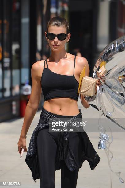 Georgia Fowler holds on to her CK shaped silver balloons as she walks in West Village on August 17 2017 in New York City