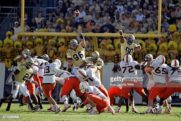 Georgia Tech defensive tackle Joe Anoai and defensive end Darrell Robertson go to the air trying to block a field goal by Miami kicker Jon Peattie in...