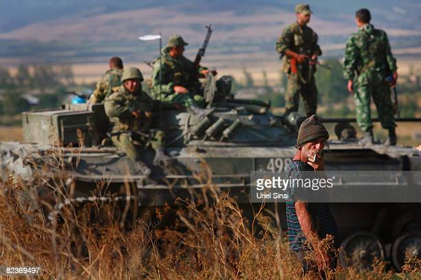 A Georgian man looks on as a convoy of Russian armour heads along the main road from Gori towards Tblisi as the tense standoff on the north of...