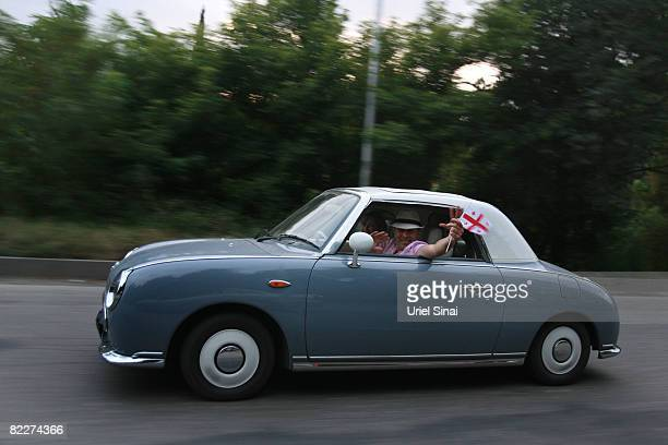 A Georgian man waves the Georgian flag as he drives on the road from Gori to Tbilisi on August 12 2008 just outside Tbilisi Georgia Russian President...