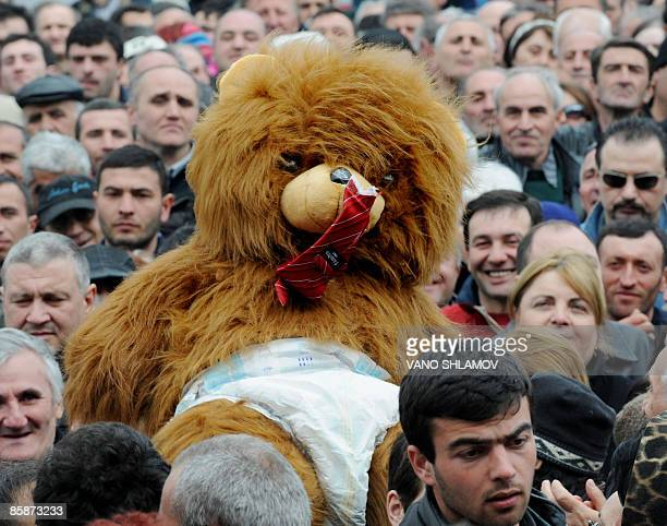 Georgian opposition protestors carry a large stuffedanimal bear wearing a diaper and chewing its tie an effigy of President Saakashvili at an...