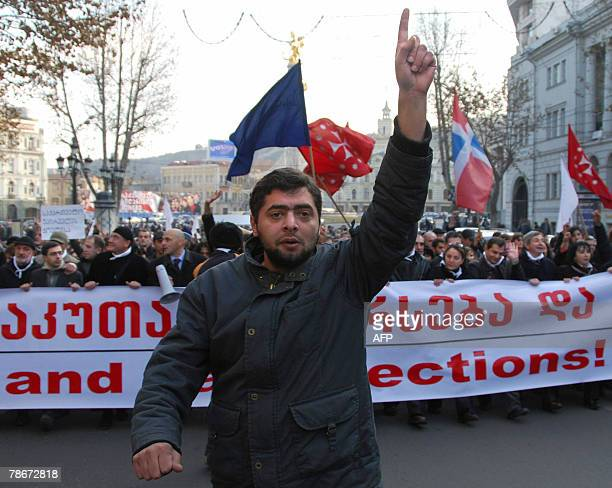 Georgian opposition supporter raises a finger as he shows the number of their candidate Levan Gachechiladze in the ballot list during a rally in...
