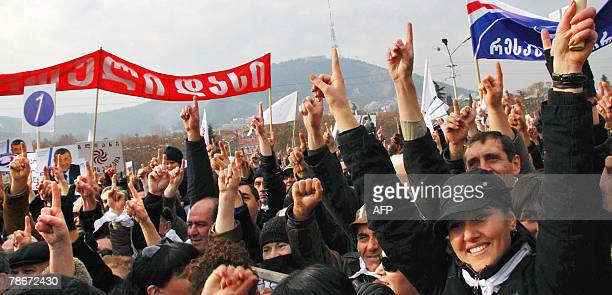 Georgian opposition supporters raise their fingers as they show the number of their presidential candidate Levan Gachechiladze in the ballot list...