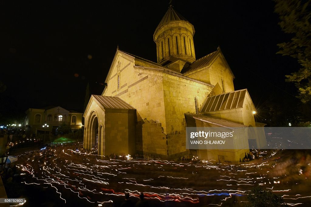 Georgian Orthodox believers holding lit candles walk around Sioni cathedral during an Orthodox Easter service in Tbilisi on May 1, 2016. / AFP / Vano Shlamov