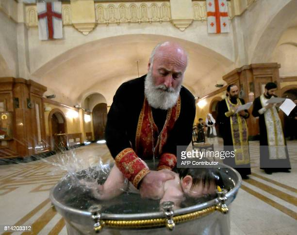 A Georgian Orthodox priest baptises a child during a mass baptism ceremony at the Holy Trinity Cathedral in Tbilisi on July 13 2017 / AFP PHOTO /...