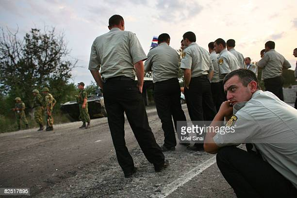 Georgian policemen wait for Russian peace keepers to let them pass the last checkpoint Russian troops control near Kharvaleti on the road from...